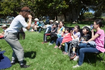 Thumper (Joan Howard) rallies a kazoo band at a performance of Shakespeare or Space Wars in San Antonio Park, Oakland. Photo by Serena Morelli