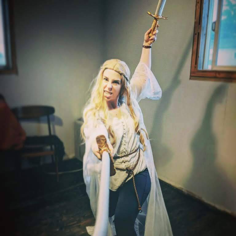 Marlene (Princess Gwen) becomes an elf queen warrior with her long blonde wig, gauzy white robe, and striking a fierce pose with a foam sword in each hand.